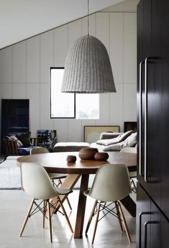 moderne wohnideen esszimmer mit schwarzer küche im offenem wohnbereich ecksofa, rundem holztisch, weißen esszimmerstühlen und hängelampe mit rattan-lampenschirm