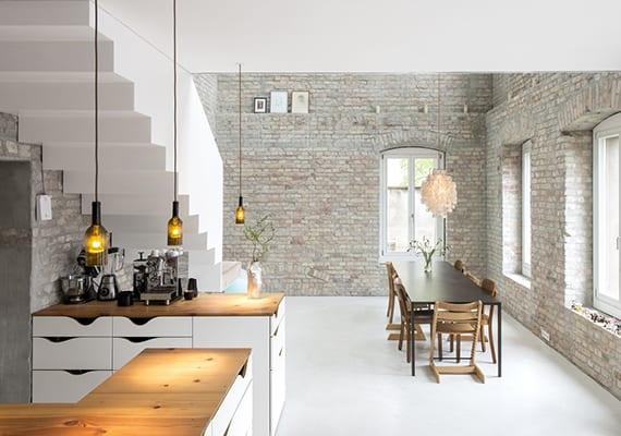 moderne offene küche weiß unter innentreppe mit weinflaschen-pendellampen, weißen ziegelwänden, weißem boden, holzesstisch schwarz