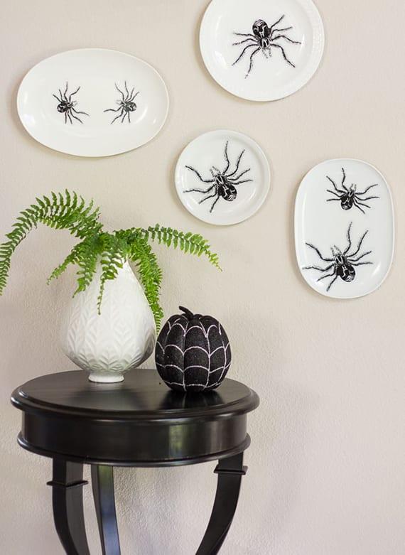 kreative Wanddeko mit weißen tellern und Spinnen-Aufklebern basteln zu Halloween