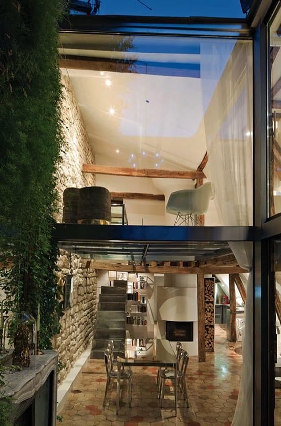modernes loft Appartement mit originellen kalksteinwand, holzbalkendecke, holudachkonstruktion, offenem Wohnesszimmer mit kleiner küche, gerundetem kamin und stahlblechtreppe