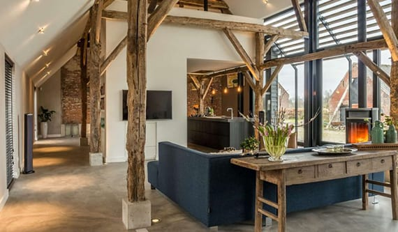 modernes haus interieur im industral style mit offenem wohnzimmer mit kochinsel, betonboden, rundem kamin, rustikalem beistelltisch holz, einbaubodenleuchten und raumhohen fenstern