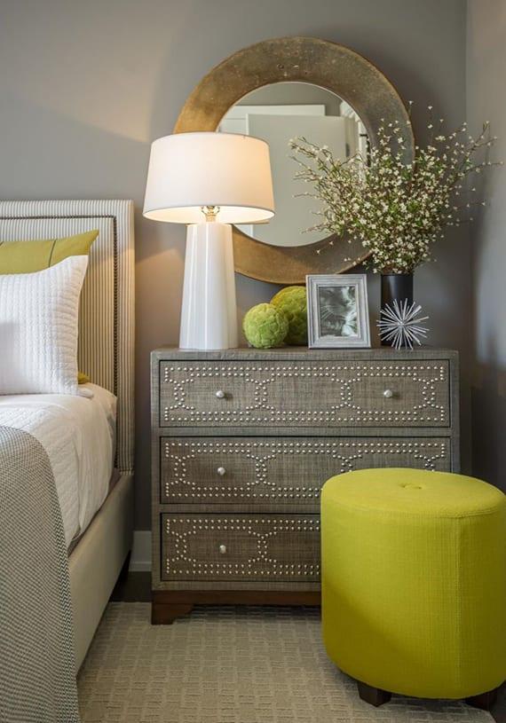 coole schlafzimmer deko mit vintage holznachttisch grau mit schubladen, rustikalem spiegel rund, moderner tischlampe weiß, rundem polsterhocker grün, wandfarbe grau