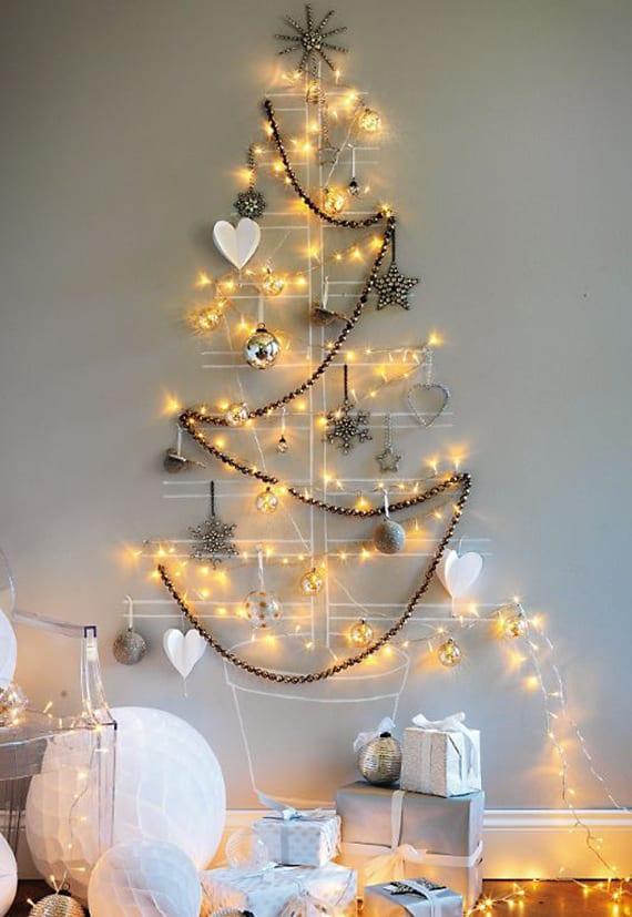 originelle wanddekoration zu weihnachten mit weihnachtsbaum aus girlanden, lichterketten und weihnachtsbaumkugeln an der wand