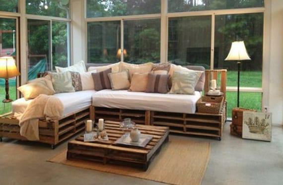 rustikales wohnzimmer design mit palettenmöbeln, alten lampen und rustikale dekoration mit kissen,weidenkorb und kleinen koffern