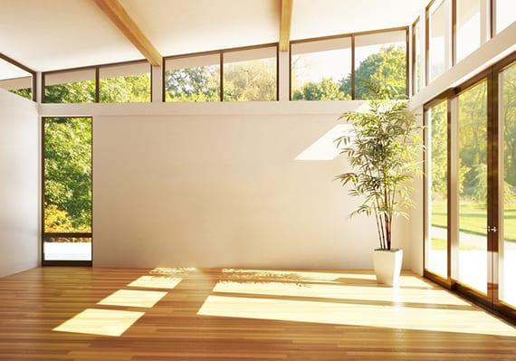 elegantes wohnzimmer interieur design mit dachschräge, holzbalken, akrchitektur fenstern mit sonderform und schwarzen fensterrahmen und parkett