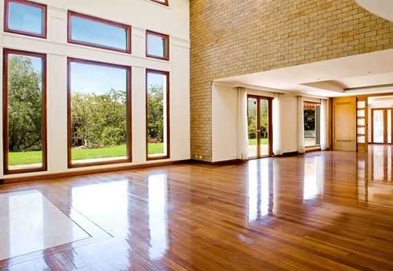 großzügiges wohnzimmer mit lackiertem parkett, wandgestaltung mit ziegeln, holz-fenster