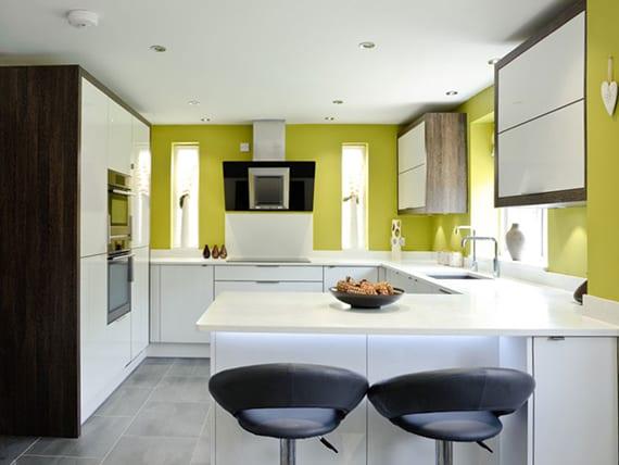 kleine weiße küche mit U-förmiger Küchenarbeitsfläche modern gestalten mit grünen wänden, dunstabzugshaube schwarz, schmalen fenstern, barhocker leder schwarz, küchenschränken weiß und holz