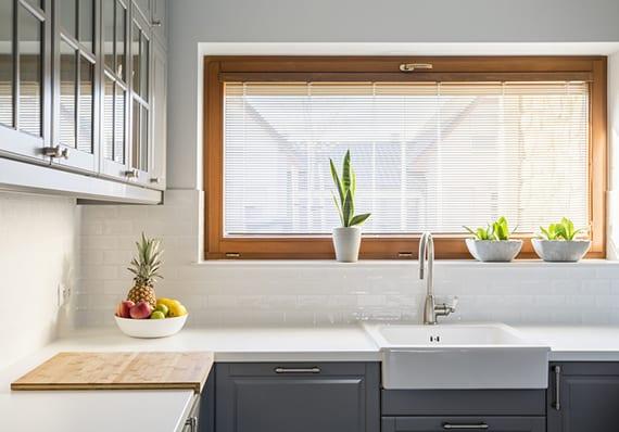 kleine küche mit holz-klappfenter vor spülbecken gemütlich einrichten mit klassischer eckküche grau, küchenarbeitsplatte weiß und frischer fensterdeko mit pflanzen