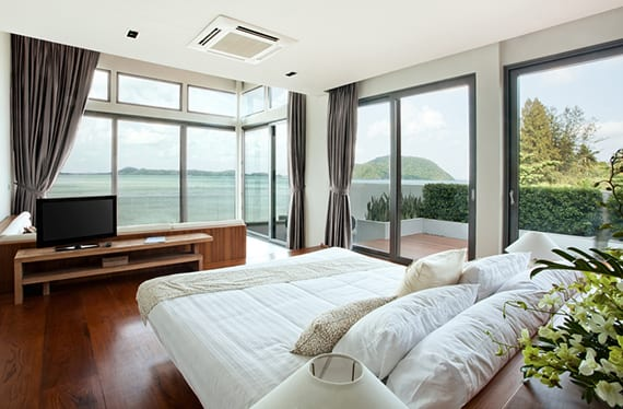 schlafzimmer gestaltung mit panorama fenstern grau, holzinterieur, ecksofa mit blick aufs meer, vorhänge grau