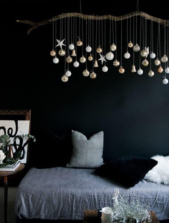 coole dekoidee weihnachten mit zweig und hängenden weihnachtsbaumkugeln in weiß und gold