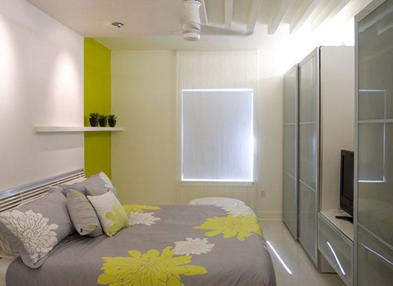 gestaltungsideen für kleines schlafzimmer weiß mit akzentwand in grüngelb, wandregal weiß, garderobe mit glastüren und bunte bettwäsche grau mit weißen und gelben blumen