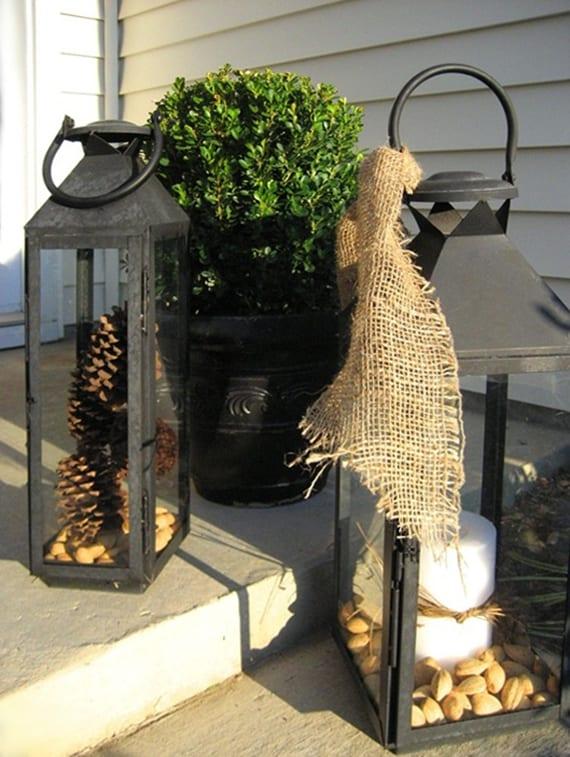 assentreppe im herbst und winter dekorieren mit zapfen und nüssen in schwarzen metalllaternen