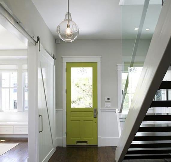 coole gestaltungsidee eingangsbereich mit wandfarbe hellgrau, holzwandverkleidung und rustikaler schiebetür weiß, metallinnentreppe weiß mit glasgeländer und eingangstür mit fenster in grün