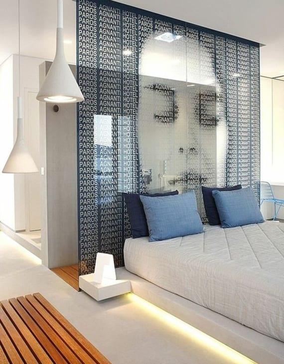 luxus schlafzimmer interieur in weiß, blau und holz mit dusche hinter glaswand, bodenbelag weiß, pendelleuchte weiß, weiß plattform bett mit blauen kissen