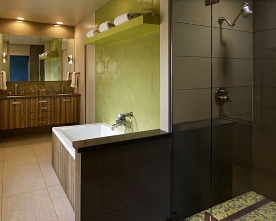 passende farben für gemütliche badgestaltung mit holzwaschtisch, dunkelbraunen badfliesen im duschbereich, grüne wandgestaltung hinter badewanne mit holzverkleidung