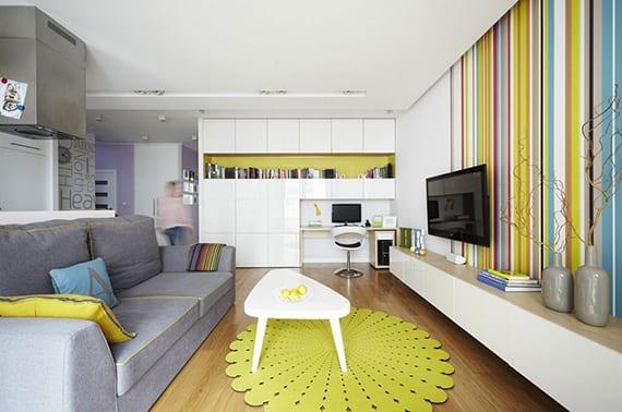 kleines wohnzimmer schick und poppig einrichten mit sofa grau, couchtisch weiß auf rundem teppich in grüngelb, hänge-tv board weiß, einbauregal weiß mit winbaubücherregal und arbeitsplatz, coole wandgestaltung und streich idee mit bunten streifen
