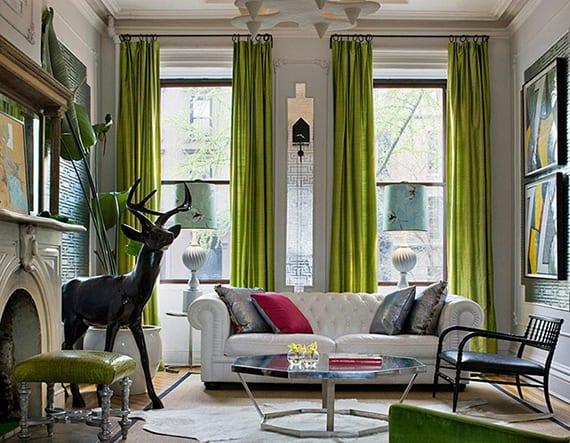 modernes und buntes interieur design für kleines wohnzimmer mit klassischem kamin, Chesterfield Sofa weiß, grünen gardinen, rundem couchtisch chrom auf kuhfell teppich weiß