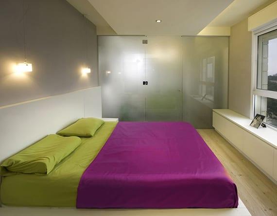 modernes schlafzimmer mit bad kreativ gestalten mit wandfarbe grau, weißem bett mit bettwäsche in grün und purpur, niedrigem regal weiß, hängelampen über bettkopfteil und glaswand