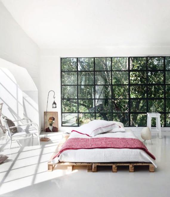 schlafzimmer modern gestalten in weiß mit sprossenfenster schwarz, paletten bett, rattansessel weiß, bettwäsche weiß, bettdecke rot