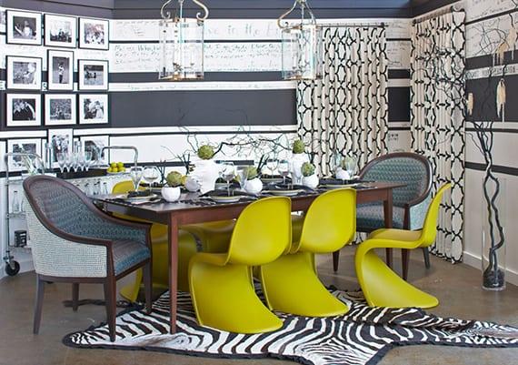 schickes esszimmer interieur in schwarzweiß mit vitra Stühlen grüngelb, individuelle wandgestaltung mit schwarzen und weißen streifen, klassischen esszimmerstühlen holz und blau, modernen hängelampen glas, wanddeko mit schwarzen bilderrahmen und betonboden