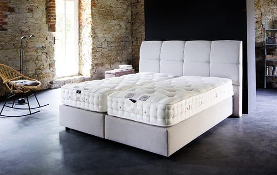 industrielles schlafzimmer mit kalksteinwänden, modernem boxspringbett in beige mit bettkopfteil gepolstert, designer schaukelstuhl rattan, moderner stehlampe schwarz, bücherregal hellblau