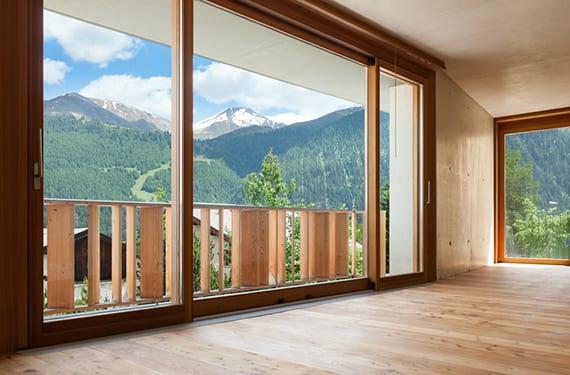 luxus schlafzimmer mit holzinterieur und panoramafesnter holz mit schiebefenstertüren zur terrasse mit holzgeländer