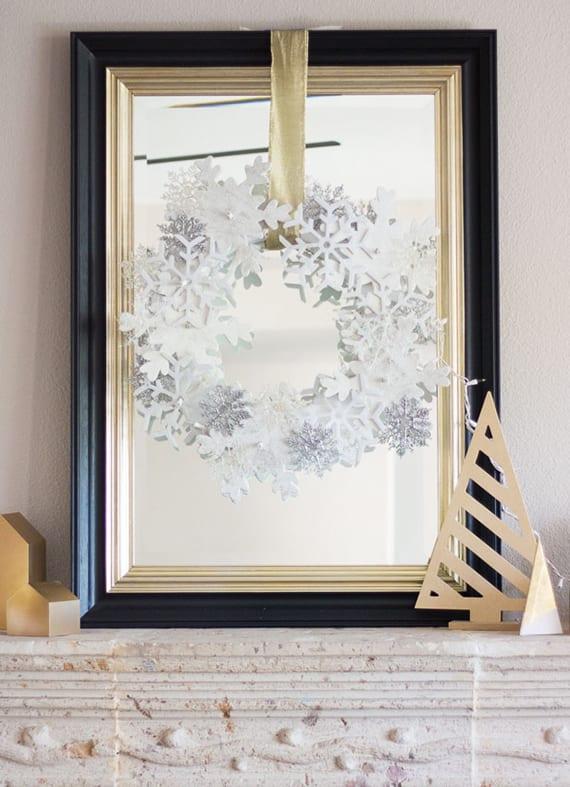 schöne kamindeko ideen zu weihnachten mit leuchtendem kranz aus schneeflocken und spigel in schwarzem rahmen