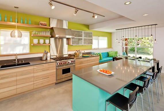 frische wohnideen küche mit betonboden, holzküchenschränken und holzwandregalen, kochinsel mit theke in türkis, akzentwand grün und moderne glaskugel-hängeleuchten über esstisch schwarz