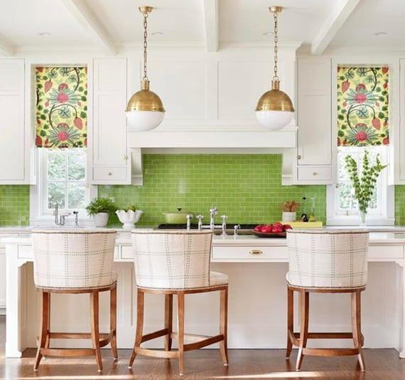 weiße küche im klassischen stil mit kochinsel und theke aus holz, polster barhocker holz, kugel-hängelampen, dunkel holzboden und spritzschutz küche aus grünen fliesen