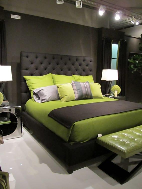 coole farbgestaltung schlafzimmer schwarz mit weißem bodenbelag, schwarzem polsterbett mit kopfteil, lederbank und bettwäsche grün, vorhänge schwarz, nachttische in chrom