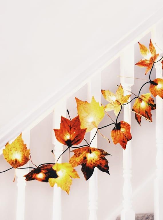 weiße innentreppe festlich und winterlich dekorieren mit DIY lichterkette aus gelben und roten herbstblättern