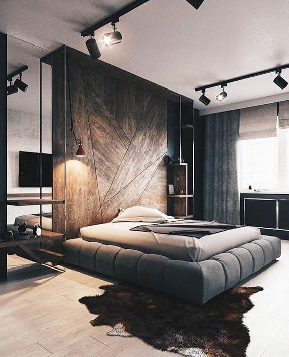 attraktive schlafzimmer gestaltung mit holzwandverkleidung, wandspiegel hinter hängenachttisch holz,wandregal holz, polsterbett mit doppelmatratze, kuhfellteppich, spot-deckenleuchten schwarz