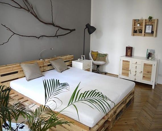 kleines schlafzimmer modern gestalten mit diy bett aus europaletten, parkett,wandfarbe grau, weißen nachttischen und kommode, stehlampe schwarz und coole wanddeko mit schwarzgestrichenem zweig