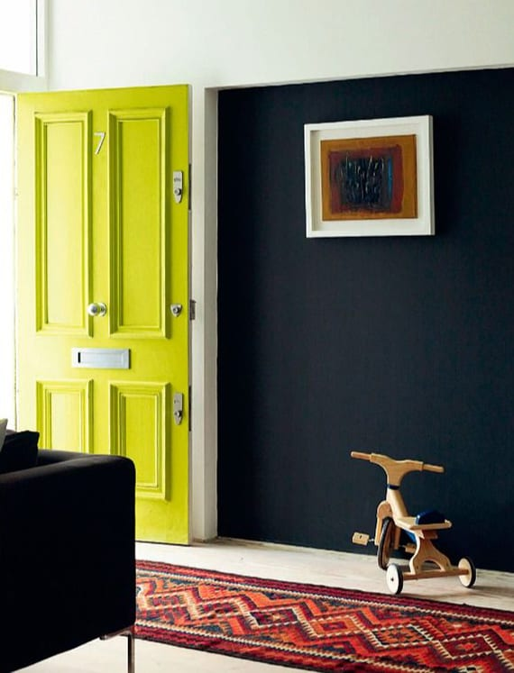 originelle wohnideen für moderne und mutige farbgestaltung mit weißen wänden,akzentwand schwarz, eingangstür in grüngelb und marrokanischer teppichläufer in rot