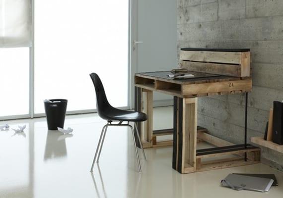 coole home office idee für einrichtung mit diy schreibtisch aus paletten und schwarzem stuhl im wohnzimmer mit betonwänden poliertem boden weiß