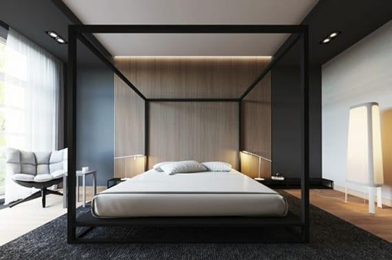minimalistisches schlafzimmer interieur design, wandfarbe schwarz, indirekte deckenbeleuchtung, metall himmelbett schwarz, akzentwand holz, teppich schwarz, designer sessel, stehlampe weiß