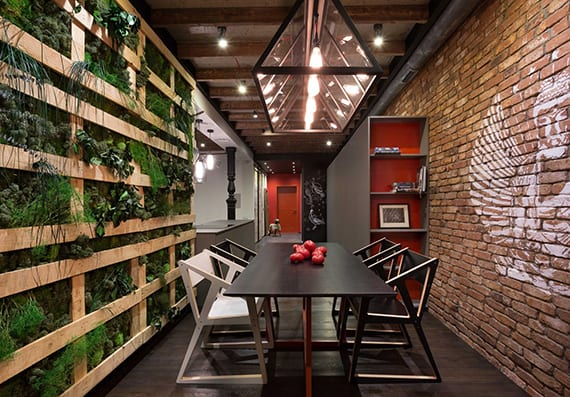 modernes interuer design einer industriellen wohnung mit ziegelwand,wandfarben grau und rot, vertikalem garten aus paletten, holzboden schwarz, offene küche mit kochinsel und modernem esstisch schwarz mit designer stühlen
