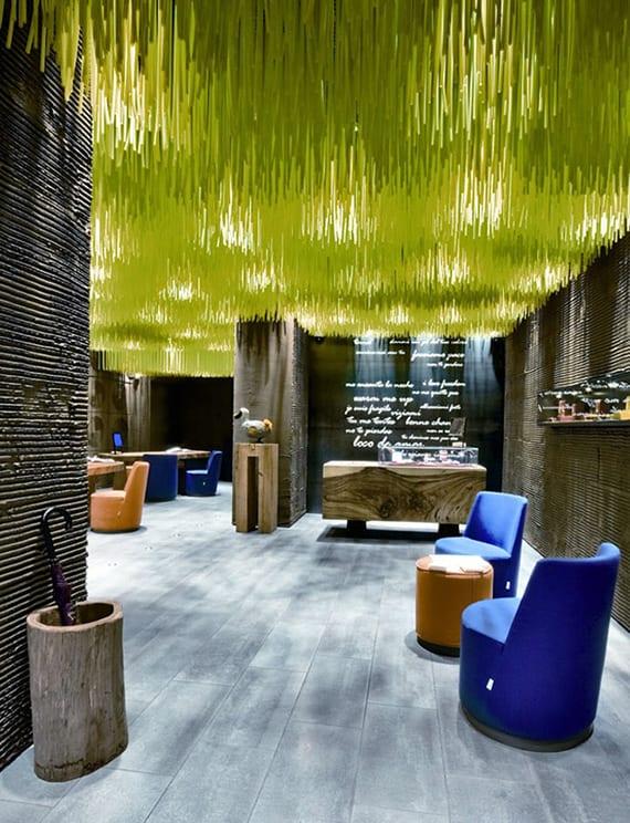 individuelle und originelle raumgestaltung mit grauem holzboden, möbel aus massivholz, runden polsterstühlen blau mit runden tischen, deckengestaltung mit hängedeko grün und reliefwandgestaltung zement