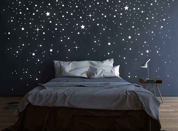 weihnachtliche wandgestaltung schlafzimmer mit fluoreszierenden Sternen auf schwarzer wand