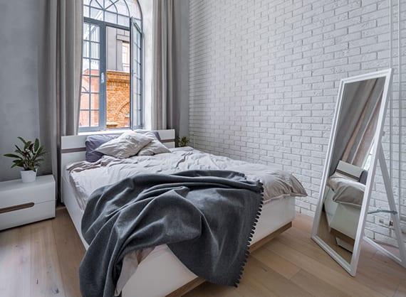 coole schlafzimmer ideen für moderne gestaltung kleiner schlafzimmer mit akzentwand aus weißen ziegeln, modernem schlafzimmer-set, Stehspiegel weiß, holzbodenbelag, wandfarbe grau,sprossenfenster rund,gardinen beige