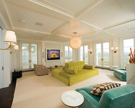 großzügiges wohnzimmer mit dopellfenstertüren stilvoll einrichten mit polstersesseln in aqua blau, barok sofa beidseitig in grüngelb, teppich beige, holzbodenbelag dunkelbraun