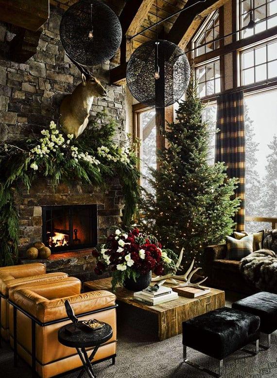 attraktive weihnachtsdeko wohnzimmer im landhausstil mit kamin aus ateinen, holzdecke, modernen kugel-hängenlampen schwarz, kaminsimsdeko mit Hirschkopg und girlande aus Grün und weißen blumen, holzcouchtisch deko mit geweihen