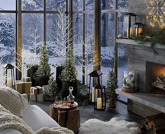 festliche und gemütliche winterdeko zu weihnachten gestalten mit kleinen beleuchteten tannenbäumen in schwarzen körben, großen laternen mit led kerzen, weißen strickdecken und pelzen, kaminholz und weißen weihnachtsbaumkugeln im runden glasgefäß