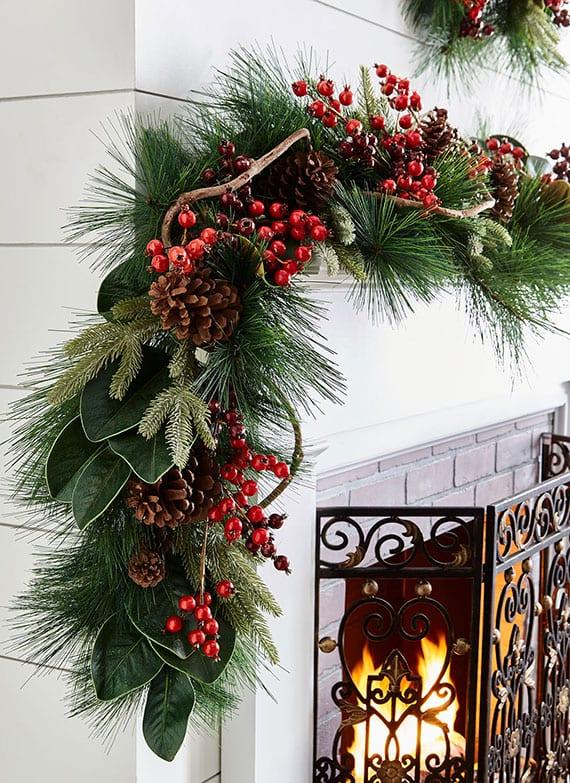 natürliche und frische weihnachtsdeko für kaminsims weiß mit girlande aus nadelbaumzweigen, grünen baumblättern, roten beerenzweigen und zapfen