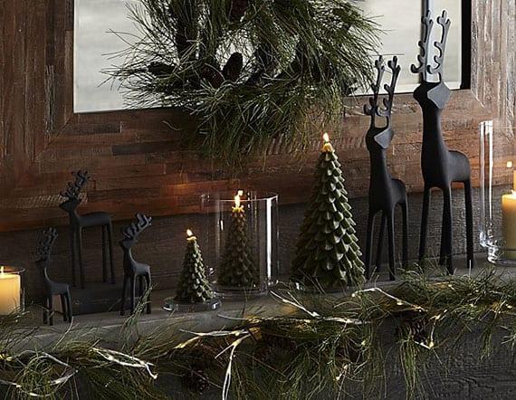 weihnachtsdeko kaminsims spigel in holzrahmen, girlande aus grün, zapfen und lichterkette, weihnachtskranz, grünen tannenbaum-kerzen und weißen kerzen in glaswindlichtern, walttierfiguren schwarz