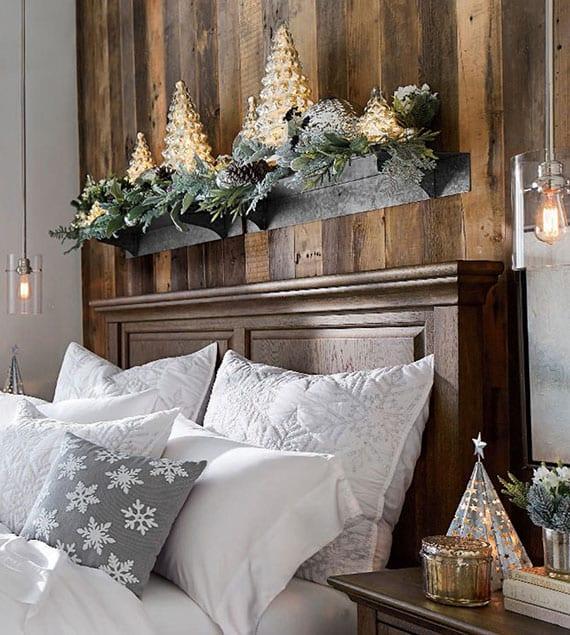 rustikales schlafzimmer mit holzwandverkleidung und massivholzbett weihnachtlich dekorieren mit festlicher bettwäsche weiß mit schneeflocken-muster, girlande aus Grün und zapfen, tannenbaim-led lampen