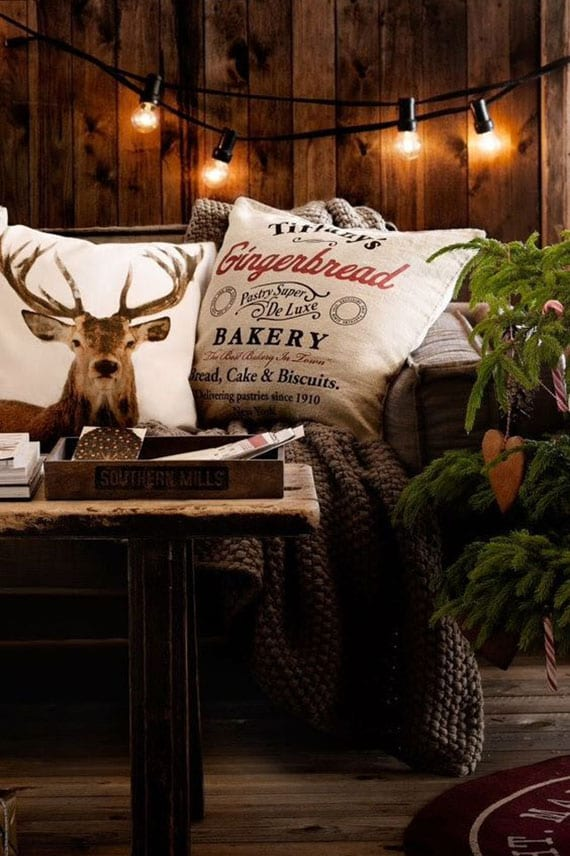 gemütliche wohnzimmerdeko zu weihnachten mit kuschelliger decke grau, gemusterten kissen, schwarzer lichterkette mit gluhbirnen als deko von holzwandverkleidung und weihnachtsbaum auf rotem teppich rund